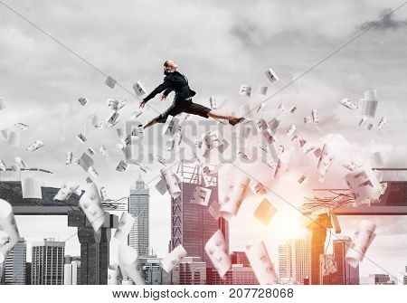 Business woman jumping over gap with flying papers in concrete bridge as symbol of overcoming challenges. Cityscape and sunlight on background. 3D rendering.