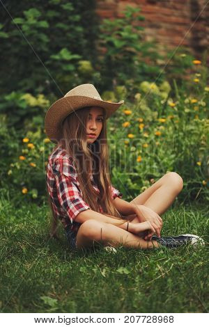 portrait of beautiful young cowgirl with long hair