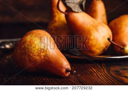Few Golden Pears with Fork and Knife on Wooden Table.