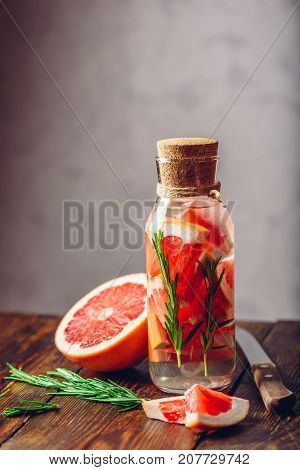 Bottle of Water Infused with Sliced Raw Grapefruit and Fresh Springs of Rosemary. Vertical Orientation. Copy Space on the Top.