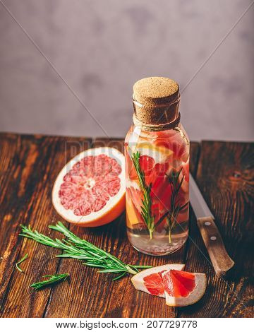 Bottle of Water Infused with Sliced Raw Grapefruit and Fresh Springs of Rosemary. Vertical Orientation.