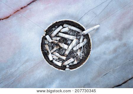 Ashtray with white cigarette red stripe litter