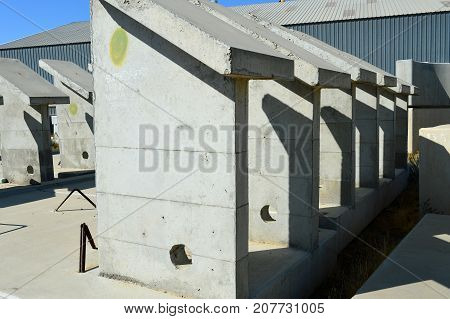 Precast concrete components of various shapes are stored in a yard awaiting incorporation into new bridge or building construction projects. poster