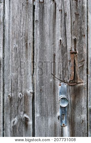 Wooden Textured Surface Of Old Door With Handle And Hook, A Lot Of Nails