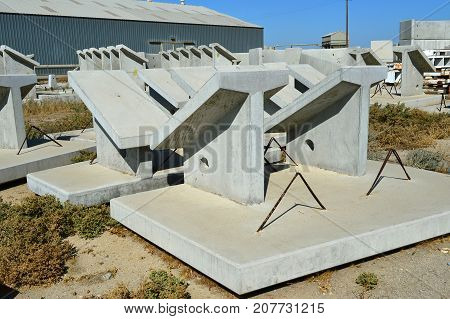 Precast concrete components of various shapes are stored in a yard awaiting incorporation into new bridge or building construction projects.