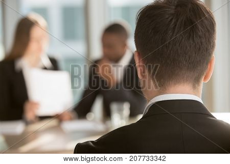White male job candidate waiting for employers decision, multinational HR managers analyzing resume on background. Man in formal wear interested in vacancy visiting job interview. Close up back view