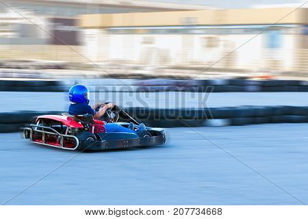 Competition karting - driver in protective form at speed passes a circle of kart trace.