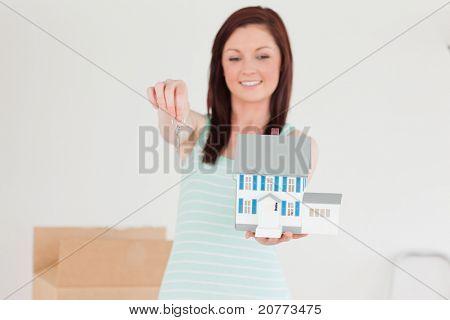 Ziemlich Rothaarige Frauen halten ein Miniatur-Haus stehen auf dem Boden zu Hause