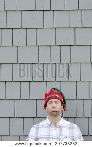 Christmas disappointment. Man with a sad face wearing a Christmas hat.