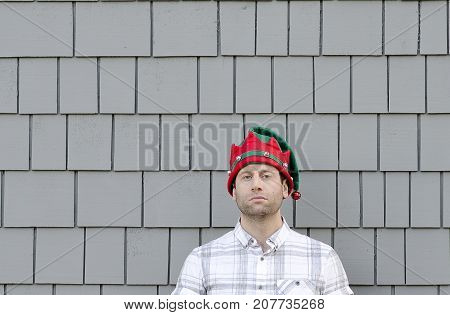 Lack of Christmas cheer. Man in a Christmas hat with no expression.