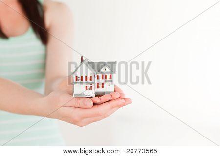 Female holding ein Miniatur-Haus stehen auf einem weißen Hintergrund