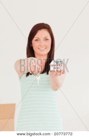Gut aussehende Rothaarige Frau hält einen Schlüssel und einen Miniatur-Haus-stand auf dem Boden zu Hause