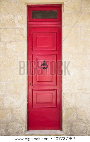 Red painted old wooden door with black iron handle in medieval city street