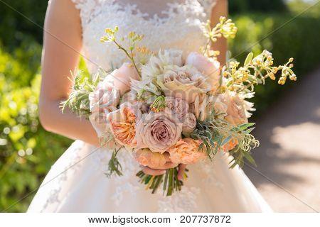 beautiful wedding bouquet of roses in bride's hands.