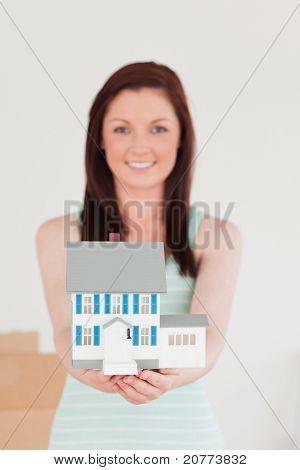 Niedliche Rothaarige Frau hält ein Miniatur-Haus stehen auf dem Boden zu Hause