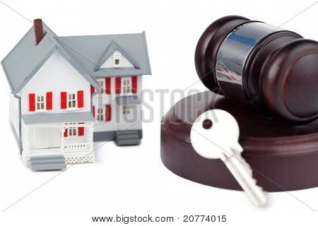 Closeup of a toy house model and a brown gavel against a white background