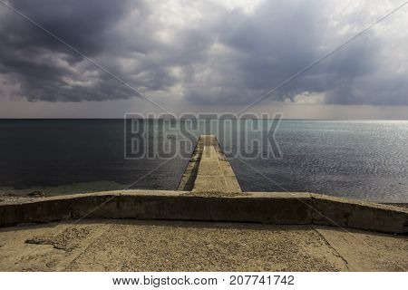 A view to concrete breakwater, a pier and sea horizon from embankment