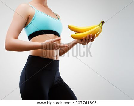 Young Sporty Girl Holding A Bunch Of Bananas. Healthy Food And Diet. The Concept Of Proper Nutrition
