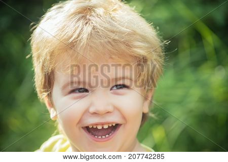 Happy boy smiling portrait. Child face with smile. Happy childhood. Joyful funny cheerful kid. Children background kindergarten. Beautiful child 3 years old. Portrait on green nature background