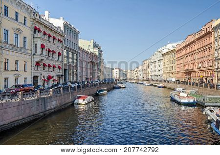 Saint Petersburg Russia - September 25 2017: View of the Moyka River from the Green Bridge with its red granite embankment many boats and the Pevchesky Bridge literally Singers' Bridge also known as Choristers Bridge or Yellow Bridge