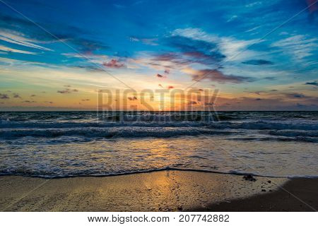 blue sky above the sun rising on the horizon and reflecting off the water on a windy morning at the beach