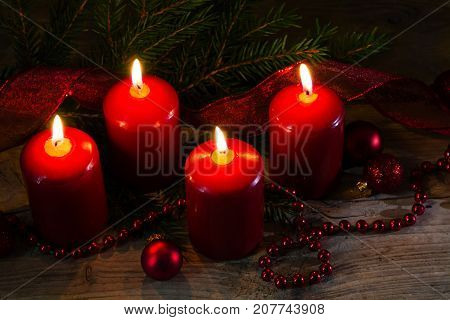 Four red burning candles at the fourth advent christmas decoration with spruce twigs and baubles on a rustic wooden table selected soft focus narrow depth of field