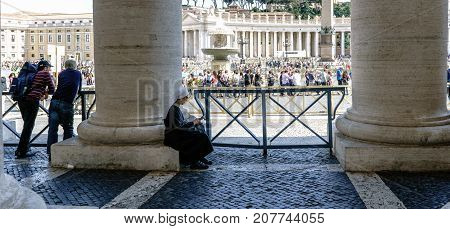 Rome, Lazio, Italy. May 25, 2017: Nun Praying Sitting On A Column Of The Arcades Of St. Peter's Squa
