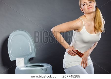 Bellyache constipation or food poisoning. Woman suffering from strong abdominal pain holding medical tablets activated carbon in hand paper on toilet in the background