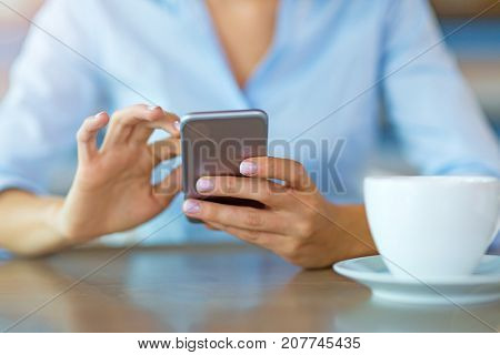 Woman using mobile phone at cafe