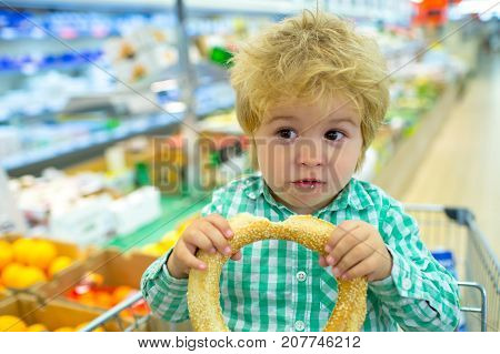 Funny Emotional Buyer In Food Store Supermarket, Boy Eats In Shopping Basket, Delicious Purchases. T