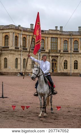 Gatchina St. Petersburg Russia - September 30 2017: Horse show of Cossacks on the parade ground of the Gatchina Palace. Cossack in a white shirt on a horse with a red flag.