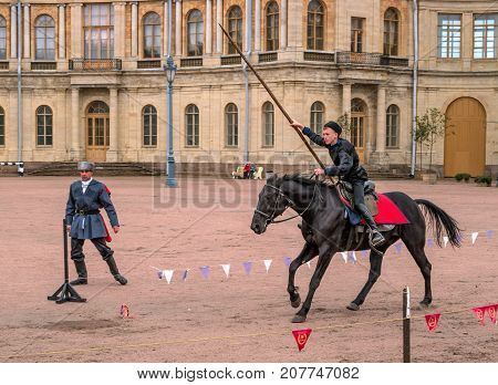 Gatchina St. Petersburg Russia - September 30 2017: Horse show of Cossacks on the parade ground of the Gatchina Palace. A Cossack on a horse jumps with a spear.