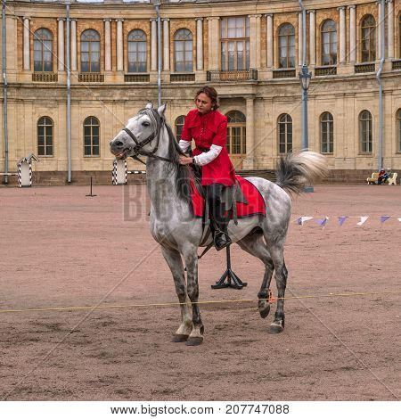 Gatchina St. Petersburg Russia - September 30 2017: Horse show of Cossacks on the parade ground of the Gatchina Palace. A Cossack girl in a red outfit on a white horse.