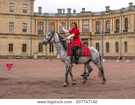 Gatchina St. Petersburg Russia - September 30 2017: Horse show of Cossacks on the parade ground of the Gatchina Palace. A Cossack girl on a white horse welcomes the audience.