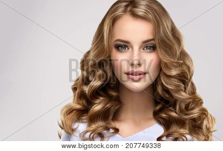 Brunette  girl with long  and   shiny curly hair .  Beautiful  model woman  with curly hairstyle. Care and beauty hair products