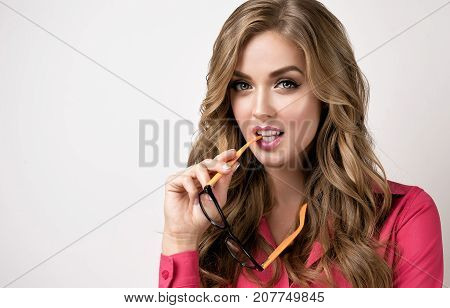 Young businesswoman or student  holding glasses in hand and smiles genuinely welcoming customer . Presenting your product. Expressive facial expressions