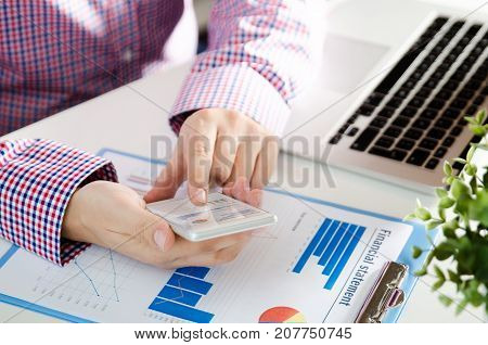 Man Using Mobile Phone While Working On Laptop