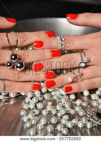 Beautiful woman hands with red pattern polish manicured nails and silver stacking rings and abstract food pearl on dark background