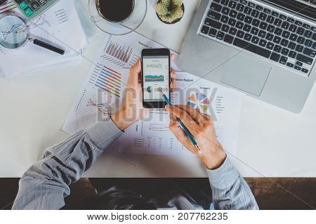 Businessman analyzing financial data on smartphone and computer screen.Business analysis and strategy concept.
