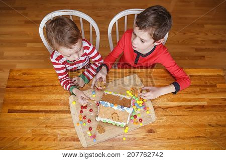 children play with homemade gingerbread house. cute brothers in Christmas pajamas sticking candies to a gingerbread house. The concept of cozy Christmas. Top view