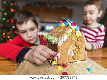 children decorate gingerbread house. lovely brothers in Christmas pajamas sticking candies to a gingerbread house. The concept of cozy Christmas