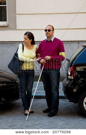Woman helps blind man on the street