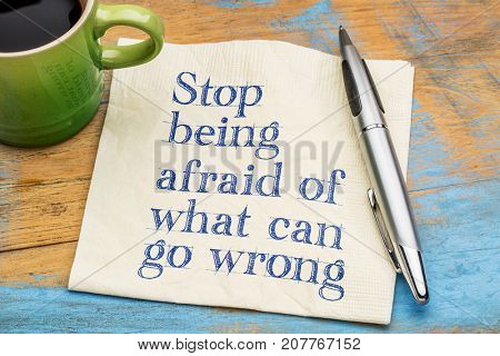 Stop being afraid of what can go wrong - handwriting on a napkin with a cup of coffee