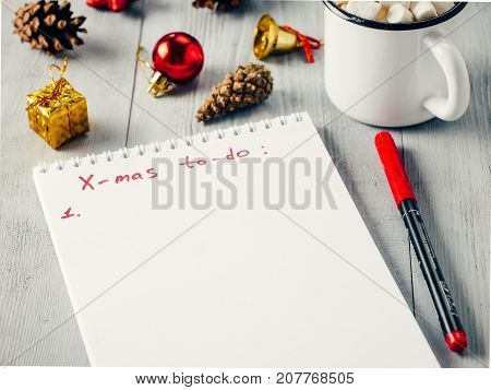 Christmas gifts shopping planning. Make shopping or to-do list for Christmas. Notebook, mug hot chocolate with marshmallows, New Year's decoration and pine cone on gray wooden background.