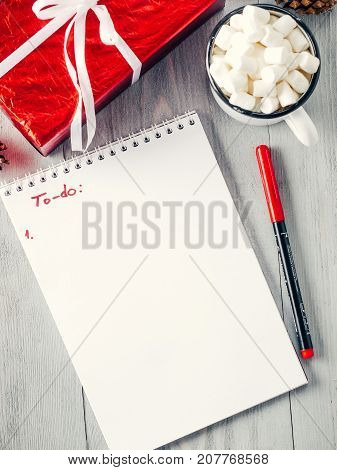 Christmas to-do list. Xmas gifts shopping planning. Make shopping or to-do list for Christmas. Notebook, mug hot chocolate with marshmallows and New Year's gift on gray wooden background. Top view