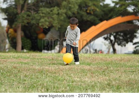 Japanese Boy Kicking A Yellow Ball (3 Years Old) On The Grass