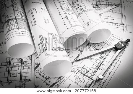Architectural blueprints and blueprint rolls and a drawing instruments on the worktable. Drawing compass plans. Civil Engineering Construction background. Black and white