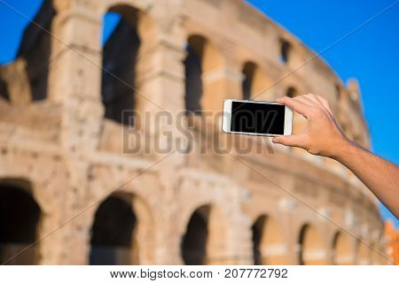 Close up cell phone in front of colosseum in rome, italy