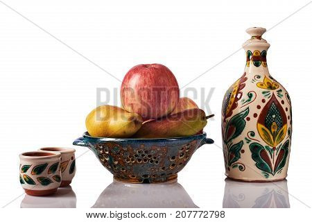 Still life with apples pears ceramic handmade bottle cups a colander. The bottle and the cup are painted according to the samples of the late nineteenth century in the technique Kosovo ceramics