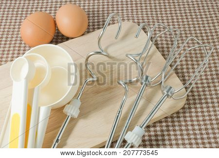 Kitchen Tools and Equipment Four Plastic Measuring Spoons in Different Sizes with Metal Whisk and Egg on Wooden Cutting Board.